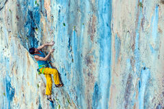 Side View of Male Climber hanging on vertical Rock Stock Photo