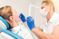 Side view on male dentist examining teeth of female patient. Helping people. Low angle shot of an experienced mature stomatologist wearing a medical mask using Stock Photo