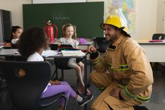 Side view of male firefighter teaching schoolkids about fire safety in classroom stock photo