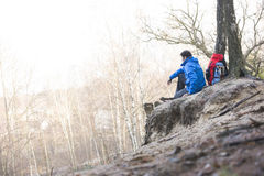 Side view of male hiker sitting on edge of cliff in forest Stock Photos
