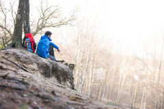 Side view of male hiker sitting on edge of cliff in forest Stock Image