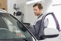 Side view of male maintenance engineer holding tablet PC while examining car in workshop stock photos