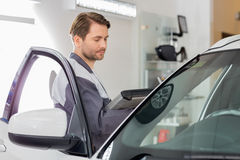 Side view of male maintenance engineer holding tablet PC while examining car in workshop Stock Image