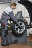 Side view of male mechanic repairing car's wheel in workshop Royalty Free Stock Images