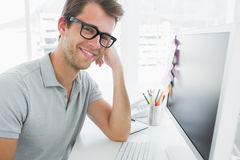 Side view of male photo editor working on computer. In a bright office Royalty Free Stock Images