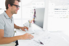 Side view of male photo editor working on computer Royalty Free Stock Images