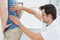 Side view of a male physiotherapist examining mans back Stock Photo