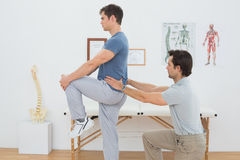Side view of a male physiotherapist examining mans back. In the medical office Royalty Free Stock Photography