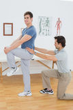 Side view of a male physiotherapist examining mans back Stock Images