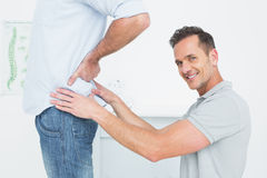 Side view of a male physiotherapist examining mans back Royalty Free Stock Photography