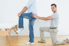 Side view of a male physiotherapist examining mans back Stock Photography