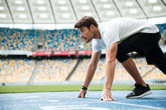 Side view of a male runner ready for sports exercise. On a racetrack at the stadium Royalty Free Stock Image