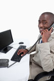 Side view of a male secretary answering the phone while using a Stock Image