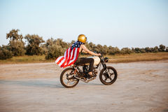 Side view of man in american flag cape driving motorcycle Royalty Free Stock Images