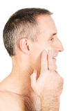 Side view of a man applying cream on his face Royalty Free Stock Images