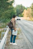 Side view of man with backpack and map standing on road while. Traveling alone stock images
