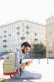 Side view of man with backpack using cell phone in city on sunny day Royalty Free Stock Photos