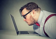 Side view of a man with bad vision having difficulty to read email. Side view of a chubby man with bad vision having difficulty to read email royalty free stock photo