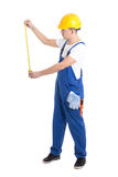 Side view of man builder in blue coveralls holding measure tape Stock Photography