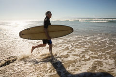 Side view of man carrying surfboard while walking on shore Stock Images
