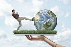 Side view of man in casual clothes kicking Earth globe, on top of digital tablet screen covered with green grass, held. In woman`s hand. Man and nature. Cause royalty free stock photo