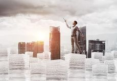 Study hard to become successful businessman. Side view of man in casual wear keeping hand with book up while standing on pile of documents with cityscape and Stock Image