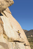 Side View Of A Man Climbing On Cliff. Side view of a young man climbing on cliff against clear blue sky Stock Photography