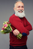 Side view of a man with a colorful bouquet of flowers. Side view shot of mature bearded man who is carrying a bouquet of flowers consisting of different tulips Royalty Free Stock Photos