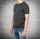 Side view of a man in a dark grey t-shirt and denims. Stock Images