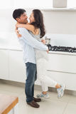 Side view of a man embracing woman in kitchen Stock Photo