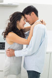 Side view of a man embracing woman in kitchen Royalty Free Stock Photos