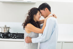 Side view of a man embracing woman in kitchen Royalty Free Stock Photo