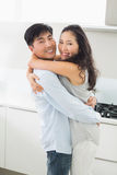 Side view of a man embracing woman in kitchen Stock Images