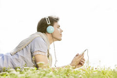 Side view of man enjoying music on MP3 player using headphones in park against clear sky Royalty Free Stock Photo