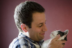 Side view of man and his cat gazing into each other`s eyes. Cat is a small Snowshoe cat Stock Photo