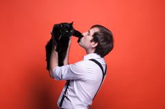 Man holding and kissing on paw black cat on orange background stock images