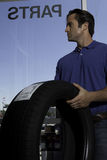 Side view of man holding tire Royalty Free Stock Photography