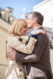 Side view of man hugging happy woman outside. Royalty Free Stock Photos