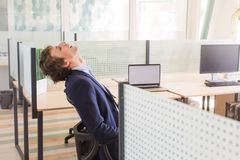 Man masturbating at work. Side view of man leaning back in chair with eyes closed and masturbating at work dreaming of erotic scenes royalty free stock images