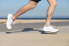 Side view of a man legs running on the concrete of a seafront. With the sky in the background stock photo
