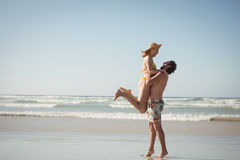 Side view of man lifting woman at beach Royalty Free Stock Images