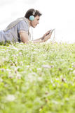 Side view of man listening to music on MP3 player using headphones while lying in park against clear sky Stock Image