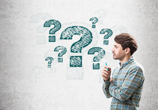 Side view of man with marker and question marks Stock Photography