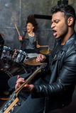Side view of man playing guitar with woman playing drums. Side view of men playing guitar with women playing drums, hard rock music concept Royalty Free Stock Photo