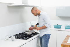 Side view of man preparing food in kitchen Stock Photography