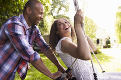 Side View Of Man Pushing Woman On Tire Swing In Garden Stock Images