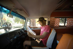 Side view of man reading map in camper van Stock Images
