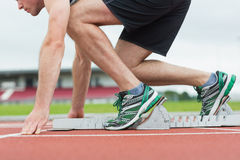 Side view of a man ready to race on running trac Stock Images