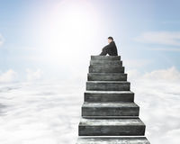 Side view of man sitting on top of concrete stairs Royalty Free Stock Photo