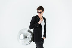 Side view of man in suit carrying disco ball Stock Photo